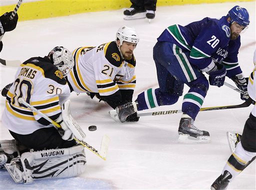 Boston Bruins goalie Tim Thomas (30) blocks a shot attempt by Vancouver Canucks left wing Christopher Higgins (20) as Bruins defenseman Andrew Ference (21) helps defend in the third period during Game 7 of the NHL hockey Stanley Cup Finals, Wednesday, June 15, 2011, in Vancouver, British Columbia. (AP Photo/Julie Jacobson)