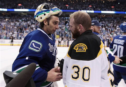 Vancouver Canucks goalie Roberto Luongo congratulates his Boston Bruins counterpart, Tim Thomas, following the Bruins' 4-0 win of Game 7 of the NHL hockey Stanley Cup Finals on Wednesday, June 15, 2011, in Vancouver, British Columbia. (AP Photo/The Canadian Press, Jonathan Hayward)