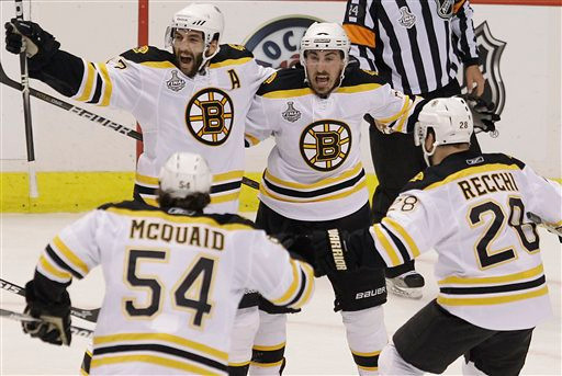 Patrice Bergeron (37), left wing Brad Marchand (63), defenseman Adam McQuaid (54) and left wing Daniel Paille (20) celebrate after a goal by Bergeron in the first period during Game 7.  (AP Photo/Julie Jacobson)