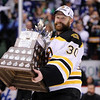 Boston Bruins goalie Tim Thomas holds up the Conn Smythe trophy after blanking the Vancouver Canucks 4-0 in Game 7 of NHL hockey Stanley Cup Finals on Wednesday, June 15, 2011. The trophy goes to the most valuable player of the postseason. (AP Photo/The Canadian Press, Jonathan Hayward)