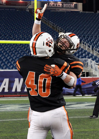 Beverly senior captain Dom Abate points skyward with one finger while being picked up by teammate Chris Vallette, left, after the Panthers defeated the Red Hawks of Natick to capture the D2A Super Bowl on Saturday evening at Gillette Stadium in Foxborough. David Le/Staff Photo