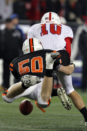 Beverly junior defensive end Zach Duguid strips the football from the grasp of Natick quarterback Troy Flutie as he scrambled out of the pocket. Duguid and the Panthers took home the school's second Super Bowl title in three years as they defeated Flutie and the Red Hawks 28-21 on Saturday evening at Gillette Stadium. David Le/Staff Photo