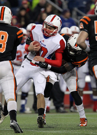 Beverly junior linebacker Sam Mulumba, right, gets two hands on Natick quarterback Troy Flutie and drags him down for a sack on the play as other Panther defenders close in. Beverly defeated Natick 28-21 in the D2A Super Bowl at Gillette Stadium on a cold Saturday night. David Le/Staff Photo