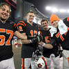 From left, Beverly High School seniors Marc Babcock, Brendan McGee, Brian Perry, and Mike Dooling hold onto a piece of rope given to each player as a symbol of team unity following the Panthers' 28-21 win over Natick to capture Beverly's second Super Bowl title in three season. David Le/Staff Photo