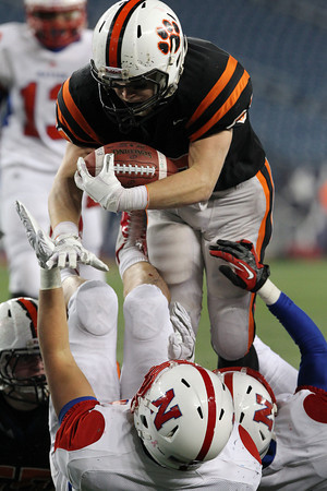 Beverly senior captain Brendan Flaherty runs over Natick's Mike Abbruzzese en route to the endzone for his first rushing touchdown of the night. Flaherty led the Panthers with 175 yards and 2 scores and helped Beverly capture their second Super Bowl title in three years with a 28-21 victory over Natick on Saturday evening. David Le/Staff Photo