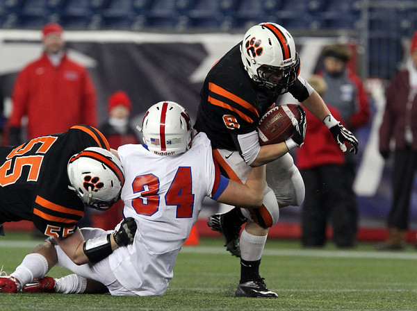 Beverly senior running back Luke McDonald, right, runs out of the arm tackle from Natick senior Zach Hilger, center, while being helped out by a block from teammate Kevin Kennedy, left, during the 4th quarter of play on Saturday evening in the D2A Super Bowl at Gillette Stadium in Foxborough. David Le/Staff Photo