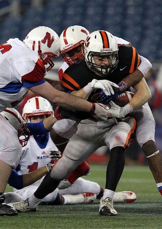 Beverly senior captain Brendan Flaherty powers through the tackle of a few Natick defenders in the second half of the D2A Super Bowl at Gillette Stadium on Saturday evening. David Le/Staff Photo