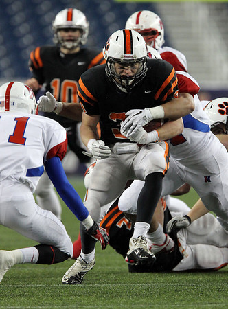 Beverly senior running back Brendan Flaherty powers through multiple Natick defenders on Saturday evening in the second half of the D2A Super Bowl at Gillette Stadium. David Le/Staff Photo
