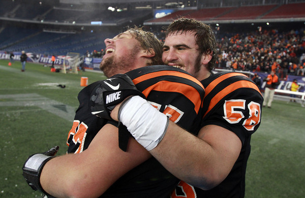 Beverly senior Brian Perry, right, hugs senior teammate Marc Babcock after the Panthers defeated Natick 28-21 and captured the Eastern Mass D2A Super Bowl Title on Saturday evening at Gillette Stadium in Foxborough. David Le/Staff Photo