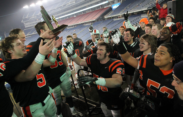 Beverly senior captain Dom Abate, left, passes the Panthers' Super Bowl trophy into the waiting hands of his teammates after Beverly defeated Natick 28-21 in the D2A title game at Gillette Stadium in Foxborough on Saturday evening. David Le/Staff Photo