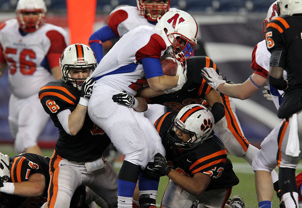 Beverly senior Luke Mcdonald, left, and junior Sean Winston, right, stuff Natick running back Nick Lee, center, for a loss in the second half of play. The Panthers made some key defensive stops and forced two Red Hawk turnovers en route to a 28-21 victory in the D2A Super Bowl on Saturday evening. David Le/Staff Photo