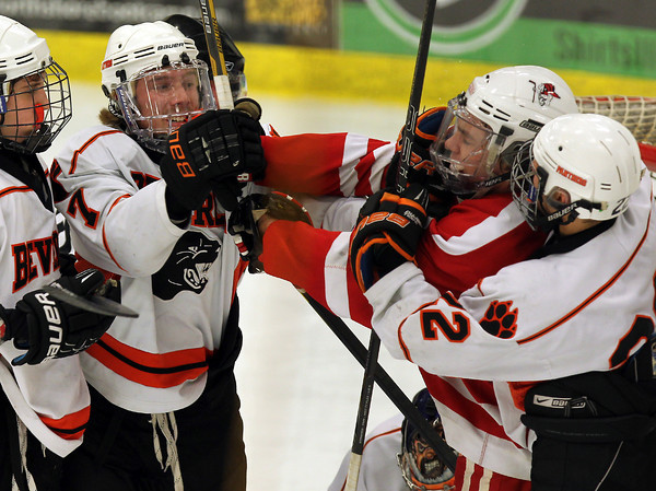 Beverly senior captain Andrew Irving, left, and Saugus sophomore Chris Sanderson, right, mix it up in front of the Beverly goal during the first period of play on Wednesday evening. David Le/Staff Photo