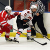 Beverly junior forward Ryan Santo, right, controls the puck along the boards and looks to pass while being pursued by Saugus senior captain Anthony LoPresti, left, on Wednesday evening. David Le/Staff Photo