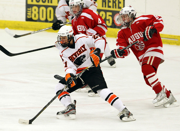 Beverly junior forward Graham Doherty, left, takes a sharp turn with the puck and throws it towards the crease while being pursued by Saugus sophomore forward Chris Sanderson, right, on Wednesday evening. David Le/Staff PhotoDavid Le/Staff Photo