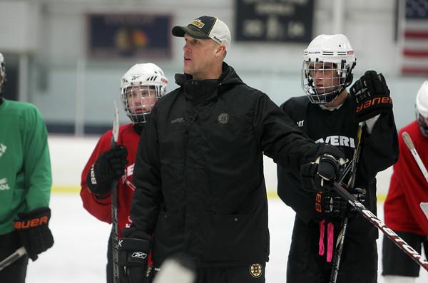 Boston Bruins Assistant Coach Doug Houda runs a drill for the Beverly High School Hockey Team at practice on Thursday evening. David Le/Staff Photo
