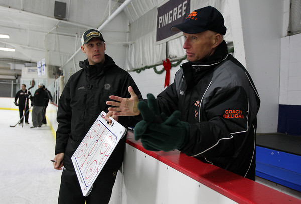 Boston Bruins Assistant Coach Doug Houda, left, listens to Beverly High School Head Coach Bob Gilligan address his team during practice on Thursday evening. Houda came to the Panthers practice and ran some drills with the team. David Le/Staff Photo