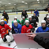 Beverly High School hockey players listen to Boston Bruins Assistant Coach Doug Houda as he runs through a drill during practice on Thursday evening. David Le/Staff Photo