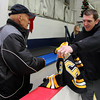 Boston Bruins Director of Media Relations and Beverly native Eric Tosi, right, presents Beverly High Head Hockey Coach Bob Gilligan with a personalized Bruins jersey after practice on Thursday evening. David Le/Staff Photo