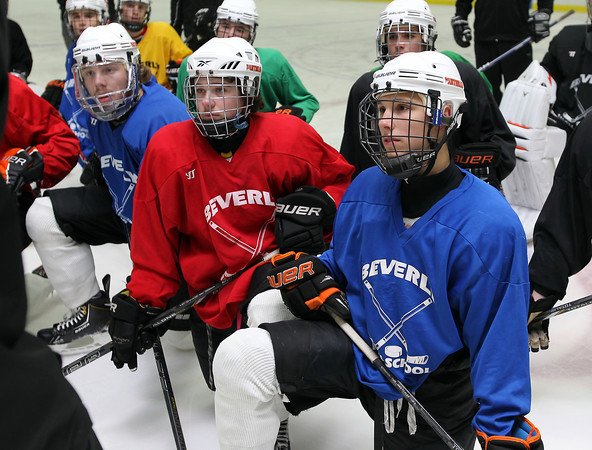 From left, Beverly High School senior captain Andrew Irving, junior forward Kevin Lally, and junior captain Connor Irving listen closely to a drill being explained by Boston Bruins Assistant Coach Doug Houda at practice on Thursday evening. David Le/Staff Photo