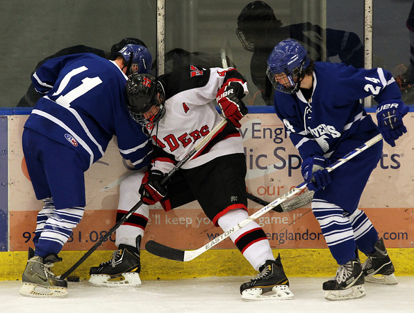 Danvers junior Jay Calcagno, left, and senior Adam Merry, right, battle along the boards for a loose puck with Marblehead junior Liam Gillis, center, during the first period of play on Saturday afternoon. David Le/Staff Photo