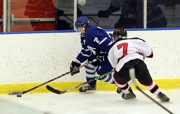 Danvers junior forward Tyler Dustin, left, brings the puck around the back of the net in the offensive zone while being pursued by Marblehead freshman Matt Koopman, right, on Saturday afternoon. David Le/Staff Photo