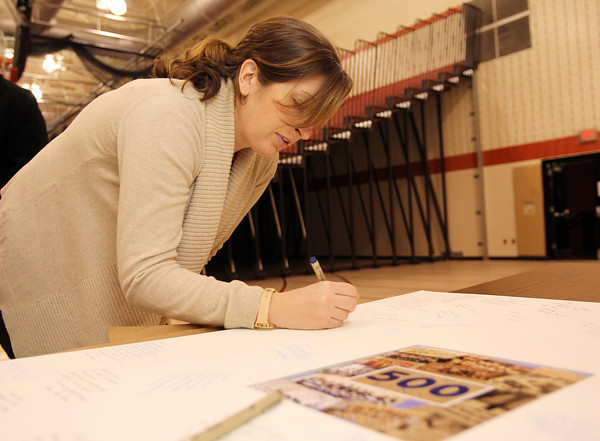 Brigid Durant, of Beverly, who played basketball with Peabody High School Head Coach Jane Heil's daughter Kristen, signs a congratulatory poster for the Peabody Head Coach after she notched her 500th career win. David Le/Staff Photo