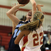 Peabody High School junior forward Carolyn Scacchi, left, winces while being fouled by Everett senior Jess Wade, right, as she drives to the basket on Thursday evening. David Le/Staff Photo
