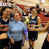 Peabody High School Girls Basketball Head Coach Jane Heil, center, gets a bouquet of flowers from junior captain Alexandra Lomasney, right, after collecting her 500th career win with a 45-28 victory over Everett on Thursday evening. David Le/Staff Photo