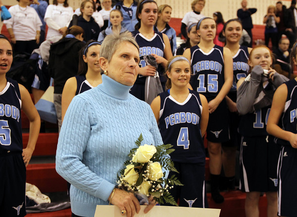 Peabody High School Head Girls Basketball Coach Jane Heil stands with her team after collecting her 500th win on Thursday night against Everett. David Le/Staff Photo
