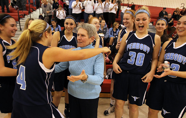 Peabody High School Girls Basketball Head Coach Jane Heil, center, gets a hug from sophomore guard Sarah Napolitano (4) after a 45-28 victory over Everett on Thursday night, notching Heil's 500th career win. David Le/Staff Photo