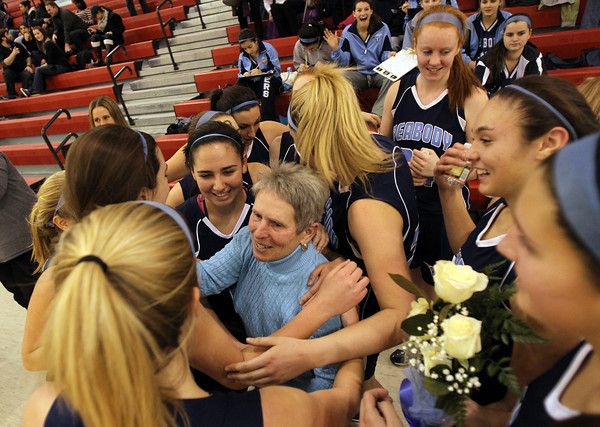 Peabody High School Girls Basketball Head Coach Jane Heil, center, gets a big hug from her team after a 45-28 victory over Everett on Thursday night, notching Heil's 500th career win. David Le/Staff Photo