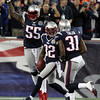 New England Patriots safety Devin McCourty, center, celebrates his first quarter interception with teammates Brandon Spikes, left, and Aqib Talib, right.  David Le/Staff Photo