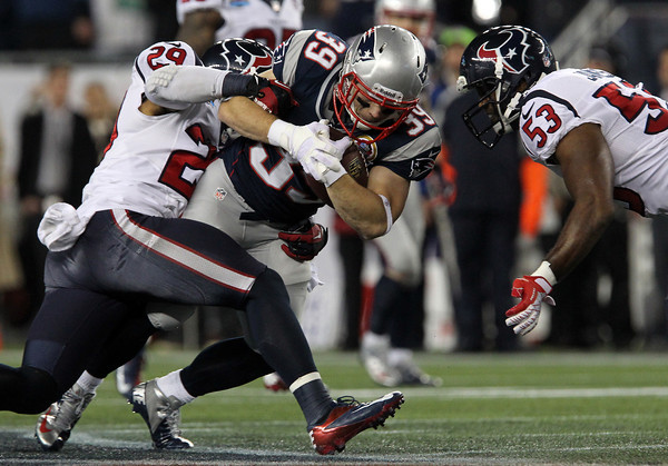 New England Patriots running back Danny Woodhead, center, braces himself for a hit from Houston Texans linebacker Bradie James, right, while being dragged down by Texan safety Glover Quin, left.  David Le/Staff Photo