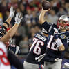 New England Patriots quarterback Tom Brady, right, fires away a pass while being pursued by Texans defender JJ Watt on Monday night. David Le/Staff Photo