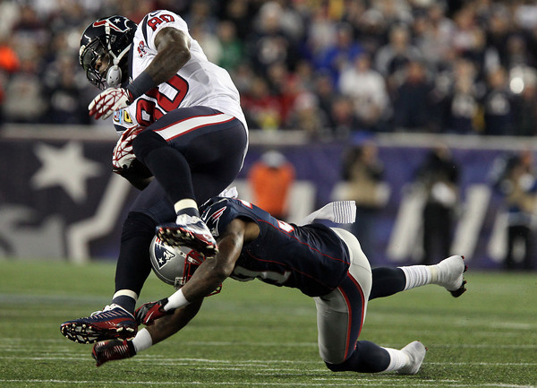 Houston Texans wide receiver Andre Johnson gets upended by New England Patriots cornerback Alfonzo Denard.  David Le/Staff Photo