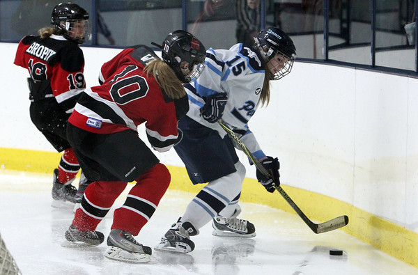 Peabody's Bella Piscatelli, right, controls the puck behind her own net while being bothered by Marblehead's Emmarose Winder, left, during the second period of play on Wednesday evening. David Le/Staff Photo