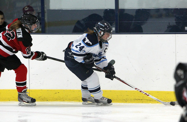 Peabody captain Courtney Smith, right controls the puck while being pursued by Marblehead's Hadley Woodfin, during the first period of play on Wednesday evening. David Le/Staff Photo