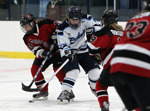 Marblehead's Emmarose Winder, left, and Peabody's Courtney Cavanaught, right, collide while battling for a loose puck on Wednesday evening at the McVann-O'Keefe Rink in Peabody. David Le/Staff Photo