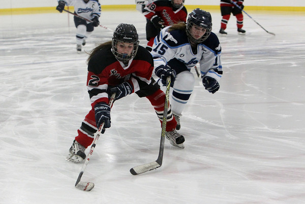 Marblehead's Halle McKay, left, holds the puck on her stick while shielding pursuing Peabody defender Bella Piscatelli, right, on Wednesday evening. David Le/Staff Photo