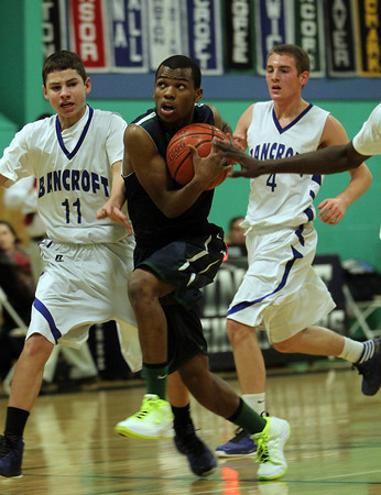 Pingree junior captain Johnny Spears protects the ball as he drives into the lane, splitting two Bancroft defenders and laying the ball in for a score. David Le/Staff Photo