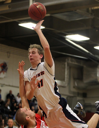 Salem State junior Trey Morin lets a shot go while running over a WPI player in the lane on Tuesday night. David Le/Staff Photo