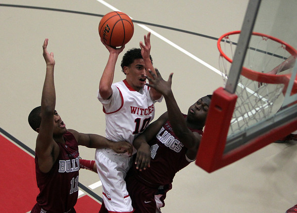 Salem High School junior guard Marvin Baez, center, splits Lynn English defenders Anthony Silfa, left, and Danny Lukanda and tries to get a shot off. David Le/Staff Photo