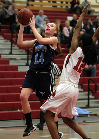 Peabody freshman point guard Sara Hosman, left, goes up for a layup while being contested by Salem freshman Maritza Scott, during the first half of play on Friday evening.David Le/Staff Photo