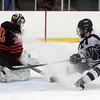 St. John's Prep junior forward Jack McCarthy sprays Woburn goalie Jeremy Flibotte, left, with snow as he tries to tip in a loose puck which slid across the crease and just wide of the net. David Le/Staff Photo