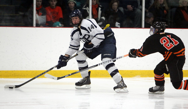 St. John's Prep junior forward Tyler Bird looks to pass the puck across ice while being pursued by Woburn's Nicholas Baldino, right, on Saturday afternoon. David Le/Staff PHoto