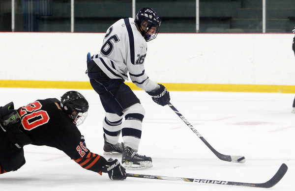 St. John's Prep senior captain Brian Pinho flips a backhanded shot past diving Woburn defender Andrew Deane, left, and past the Woburn goalie for a late third period goal. Pinho's goal sealed a 4-2 win for the Prep on Saturday afternoon. David Le/Staff Photo
