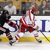 Boston: Boston University forward Sam Kurker fights for the puck along the boards with Northeastern forward Zak Stone, left, during the second period of play. David Le/Salem News