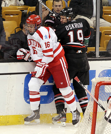 Boston: Boston University freshman winger Sam Kurker puts a hard check on Northeastern sophomore defenseman Ben Oskroba, right, during the Terriers 3-2 loss to the Huskies in the first game of the 2013 Beanpot. David Le/Salem News