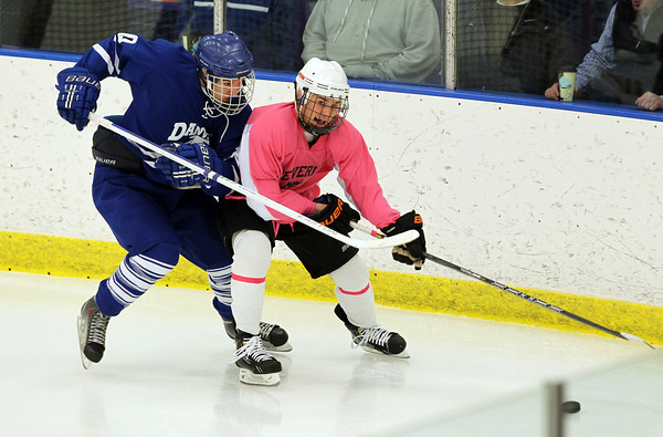 Salem: Beverly junior forward Ryan Santo sets his edges and shields the puck along the corner boards while being closely pursued by Danvers senior defenseman Kevin Anderson, left, on Wednesday evening. David Le/Salem News