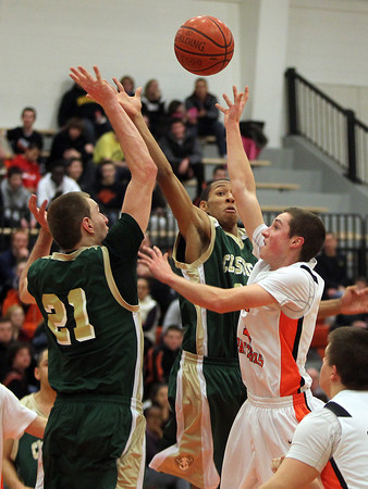 Beverly: Beverly junior Craig Hall, right, lets go of a floating jump shot in the lane ahead of the block attempts from Lynn Classical senior Eraldo Custodio, left, and Phillip Rogers, center, on Friday evening. David Le/Salem News